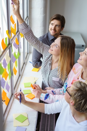 Multiple different people writing and placing down many multicolored sticky notes on a very large window