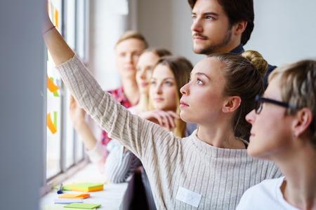 Una squadra di colleghi di lavoro concentrati che sviluppano idee e brain storming con note adesive su una finestra dell'ufficio.