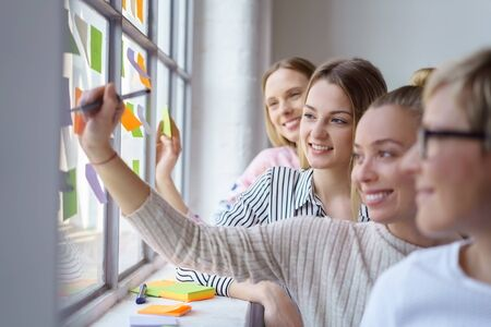 A team of happy, smiling work colleagues building ideas with sticky notes on an office window.
