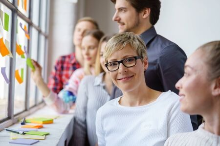 A portrait of a smiling woman wearing glasses in a happy team office environment while discussing ideas with sticky notes. Stock Photo