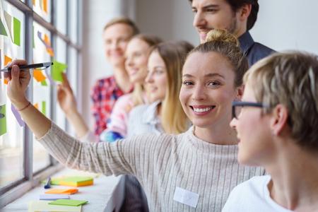 Una squadra di colleghi di lavoro felici e sorridenti che costruiscono idee e brain storming con le note appiccicose su una finestra dell'ufficio.