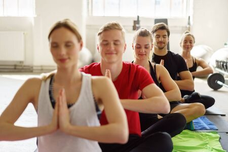 A group of five friends meditating together in a brightly lit gym after a group yoga lesson. Stock Photo