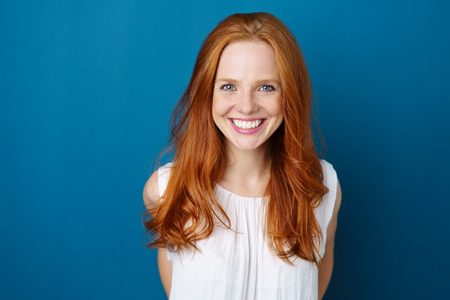 Portrait of young red-haired smiling woman against blue background