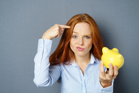 Charismatic young woman making a shooting gesture pointing her finger at her head as she pulls a wry face while holding up her piggy bank