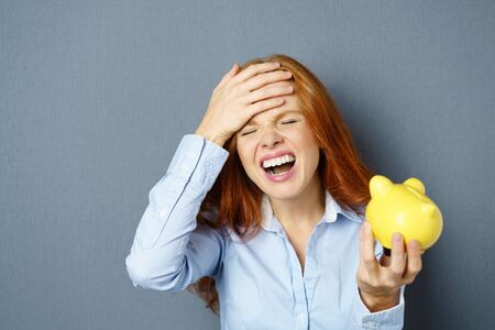 Forgetful young woman beating her forehead with her hand as she admonishes herself while holding a yellow piggy bank in her hand over a blue studio background with copy space