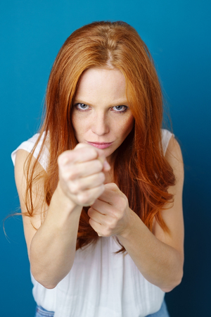 Young red-haired woman standing in fighting stance with clenched fists against blue background