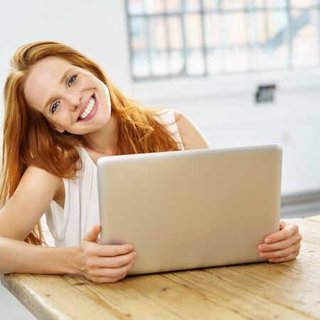 Young smiling red-haired woman using laptop while sitting at wooden desk Stock Photo