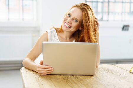 Lovely young woman with gorgeous red hair sitting working on a laptop at a wooden table grinning happily at the camera Stock Photo