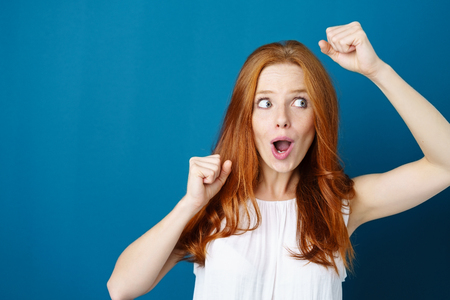 Exuberant young woman cheering and punching the air with her fists as she glances to the side over a blue studio background with copy space