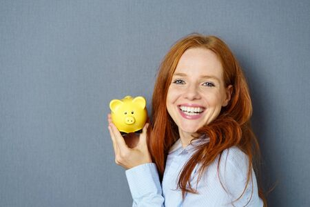 Portrait of young cheerful red-haired woman holding piggy bank against blue background