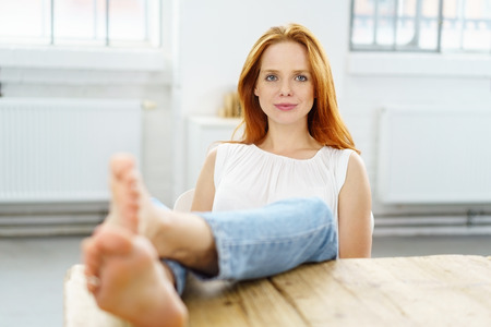 living room window: Friendly attractive young woman relaxing at home with her bare feet up on the table and focus to her face Stock Photo