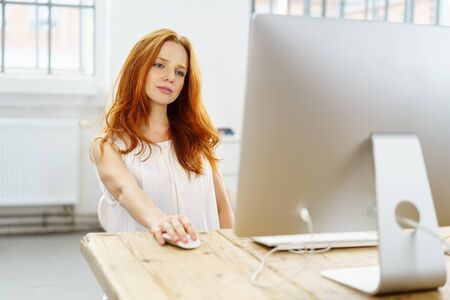 Attractive young woman reading on a computer monitor on an old wooden table viewed from behind the screen