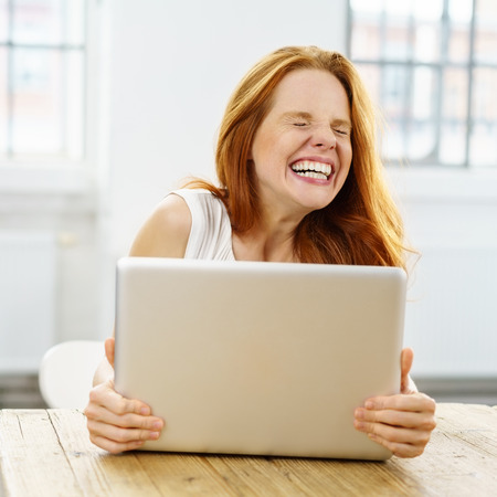 Charismatic young woman with a big toothy smile gripping her laptop as she sits at a wooden table in a high key office