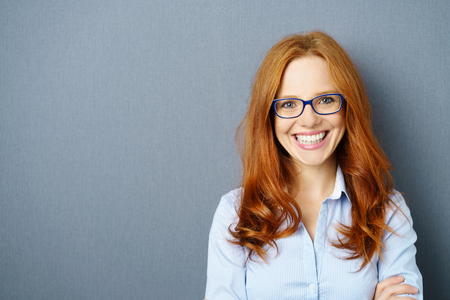 Portrait of young red-haired woman wearing glasses against blue background Stok Fotoğraf