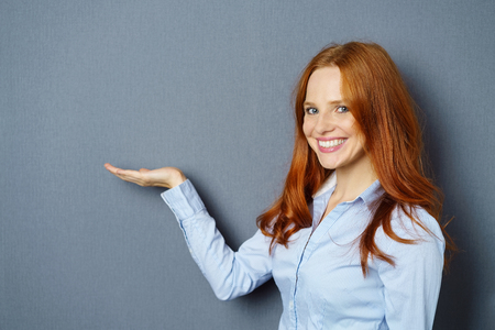 Smiling young woman holding out her hand with the empty palm up over blank copy space for your product placement