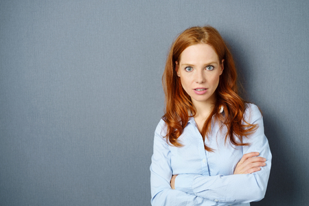 Irate young woman glaring at the camera with an intent expression and folded arms over a blue studio background with copy space