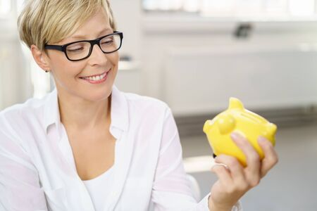 Happy young woman holding a little yellow piggy bank in her hands with a smile as she anticipates spending her savings Banco de Imagens