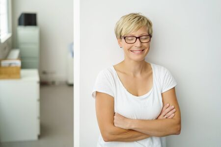 Happy woman smiling with closed eyes as she stands leaning against an interior white wall