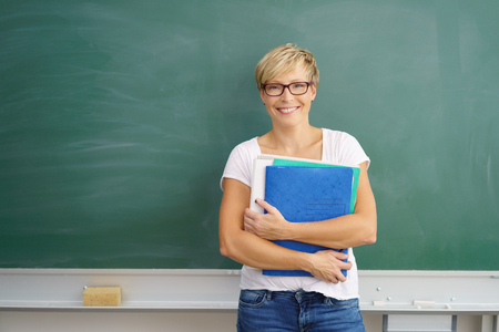 Friendly young student or teacher holding files leaning against a blank chalkboard with copy space with a happy smile Stock Photo