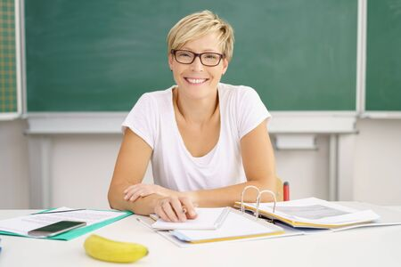 Smiling mid-adult female teacher wearing glasses sitting at desk in classroom against blackboard