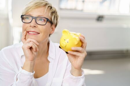 Thoughtful young woman planning a vacation or spending her savings on one of her dreams as she sits holding the piggy bank and looking into the air with a smile Stock Photo