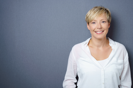 Attractive young blond woman with a friendly smile in an upper body portrait over a grey background with copy space