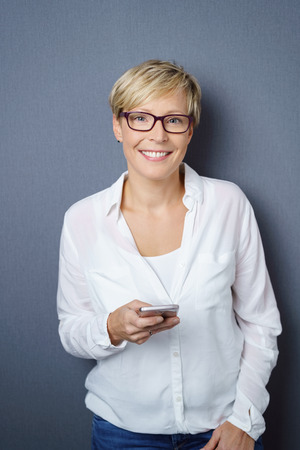 Mid-adult cheerful woman wearing glasses holding mobile phone standing against dark background