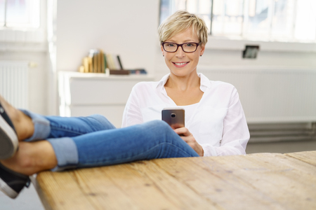 Smiling woman relaxing with her feet on a table holding her mobile phone in her hands as she smiles at the camera