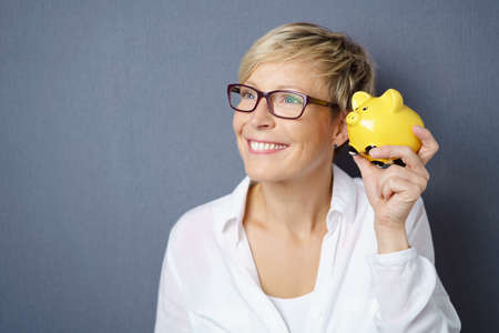 Cute young woman holding up her piggy bank close to her ear with a happy smile of anticipation as she plans spending her savings over grey with copy space Stock Photo