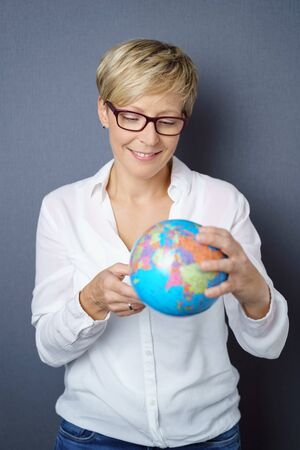 Smiling young woman holding a world globe as she searches for a fun destination for her summer vacation Stock Photo