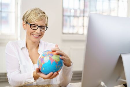 Young businesswoman holding a world globe with a happy smile as she anticipates her summer travels on vacation