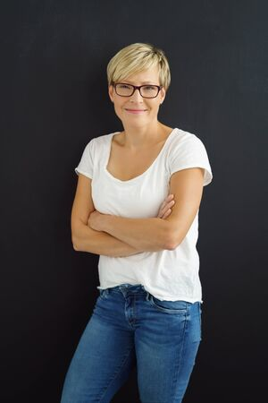 Friendly casual young woman wearing glasses and blue jeans standing with folded arms grinning at the camera isolated on black Stock Photo