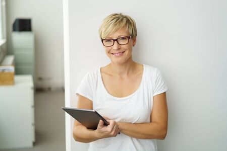Friendly young woman holding a tablet computer standing in front of a white interior wall smiling at the camera