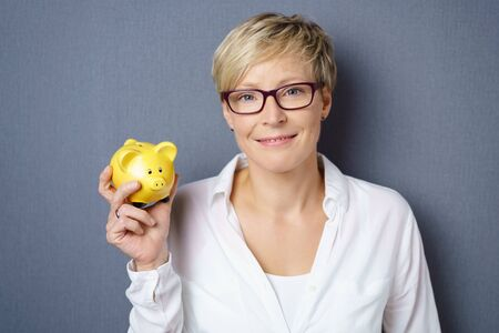 Smiling young blond woman wearing glasses holding up a yellow piggy bank in her hand over a grey background with copy space