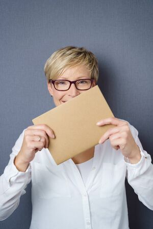 Smiling happy adult woman with glasses wearing white shirt holding blank brown piece of paper in front of her face