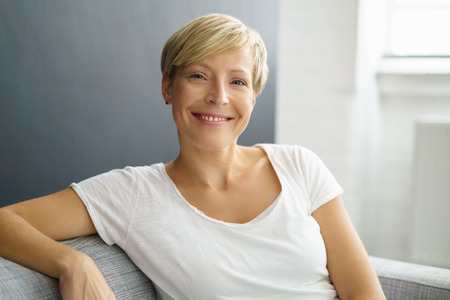 笑顔快活な広い幸せな笑顔でソファの家でリラックスする魅力的な若い女性 写真素材