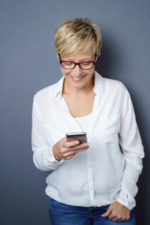 Pleased young woman reading a text message on her mobile phone with a happy smile over a grey background Stock Photo