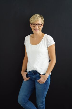 Relaxed trendy young woman in jeans standing with crossed legs and her thumbs hooked into her pockets grinning at the camera over black