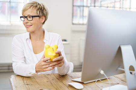 Successful young businesswoman holding a yellow piggy bank in her hands as she sits at her desk looking to the side with a smile