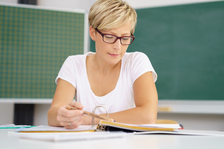 Attractive young university student wearing glasses sitting at a desk studying in the classroom with blackboard behind her Stock Photo