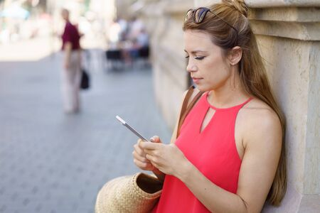 Young woman reading a text message on her mobile phone as she pauses in an urban street to lean against a wall