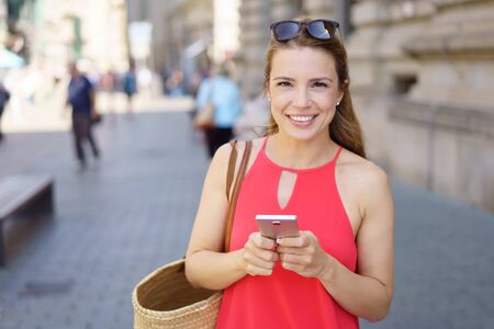 Happy attractive friendly young woman with a cheerful smile standing in an urban street with her phone in her hands