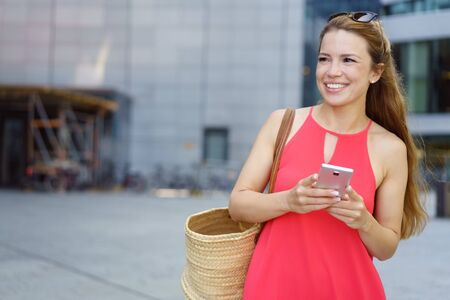 Happy young woman with a lovely smile standing in an urban street looking to the side with her mobile in her hands