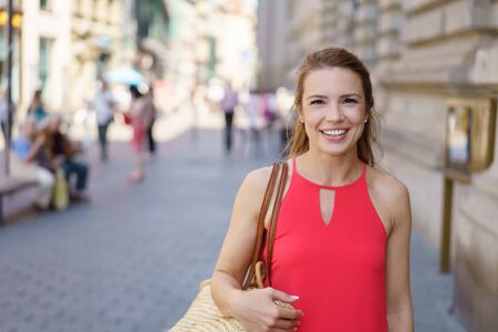 Friendly young woman walking down a street in town looking at the camera with a warm smile