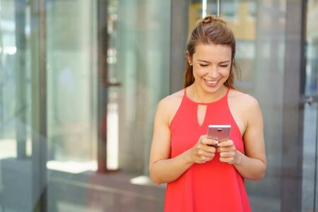 Happy young woman smiling with pleasure as she stands in an urban street reading a text message on her mobile