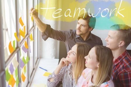Happy office colleagues brainstorming ideas using sticky notes in a teamwork themed concept with handwriting over the top. Stock Photo