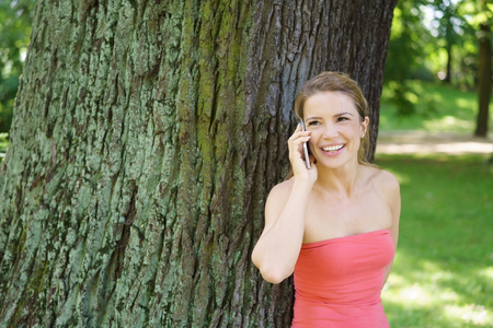 Portrait of young cheerful woman talking on mobile phone while leaning against tree