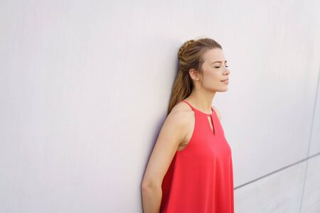 Serene young woman taking a moment to relax leaning against a white exterior wall with her eyes closed and copy space