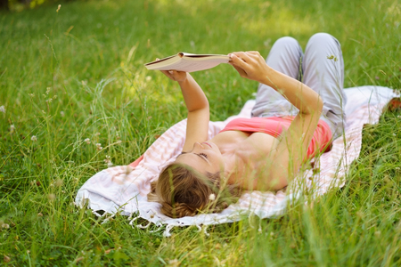 Young woman lying on her back on a rug on the grass reading a book as she spends a relaxing weekend outdoors