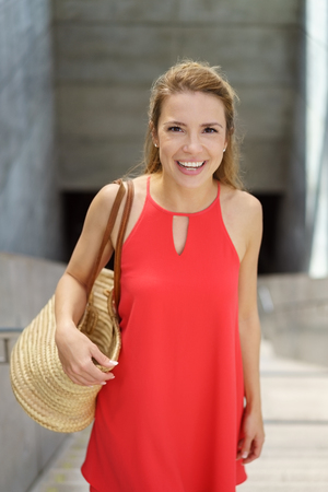 Attractive fashionable young woman in a colorful red outfit carrying a large handbag looking up at the camera with a cheerful smile Stock Photo